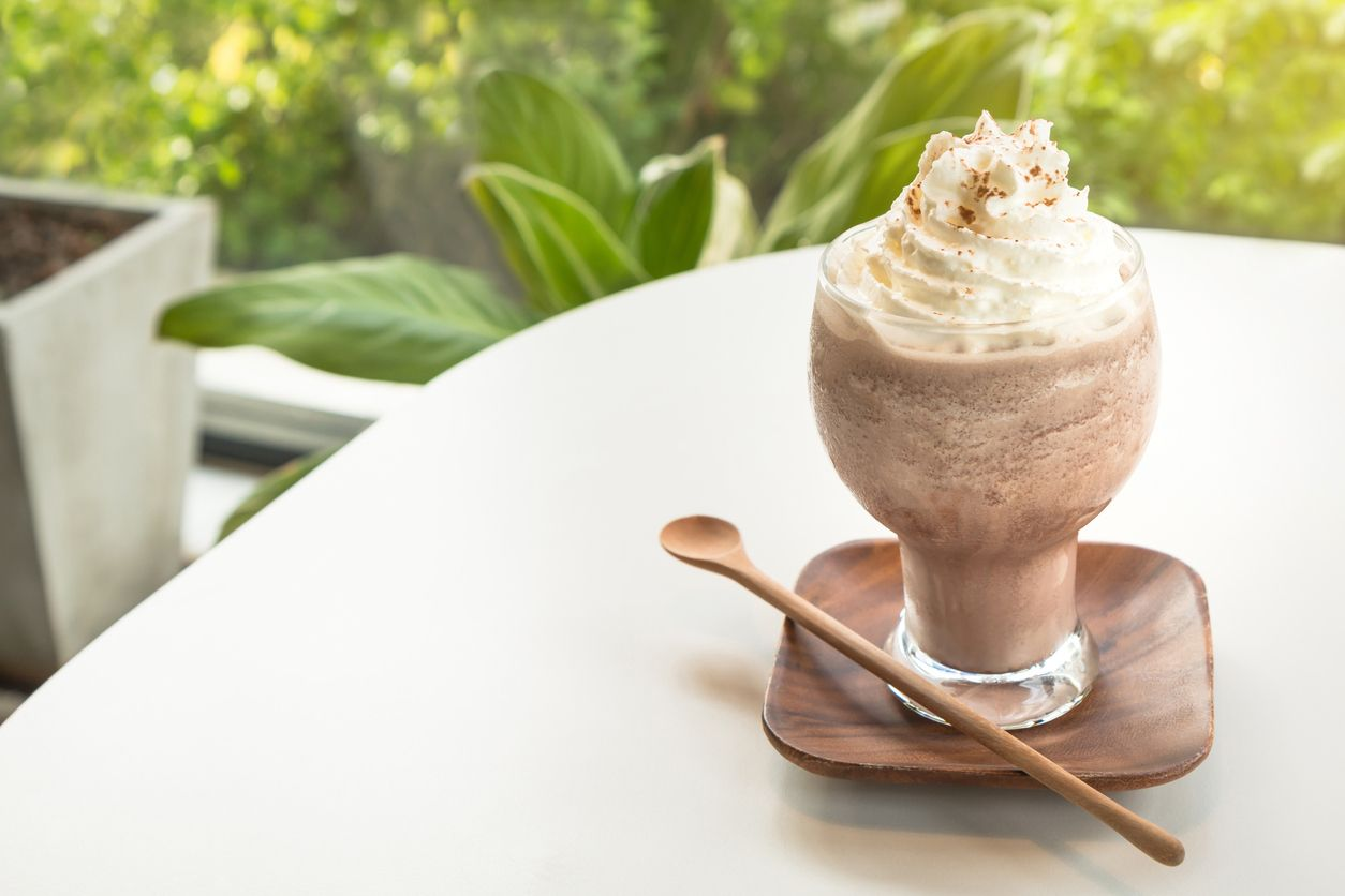 Chocolate smoothies (Cocoa blended) topped with whipped cream and cocoa powder in glass cup on white table. Wooden saucer and spoon. Interior coffee shop.