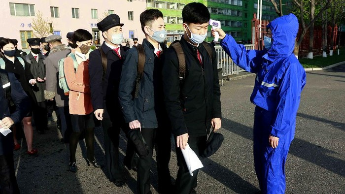 Students wearing a face mask have their temperature checked as a precaution against a new coronavirus as their university reopened following vacation, at Kim Chaek University of Technology in Pyongyang, Wednesday, April 22, 2020. (AP Photo/Jon Chol Jin)