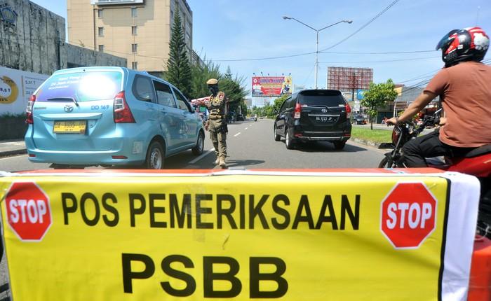 Petugas memeriksa penumpang di dalam kendaraan yang melintas di Posko Check Point Pembatasan Sosial Berskala Besar (PSBB) di Air Tawar, Padang, Sumatera Barat, Rabu (22/4/2020). PSBB diterapkan di Padang dan kabupaten/ kota lain di provinsi itu mulai Rabu (22/4/2020) hingga 5 Mei 2020 untuk menghentikan penyebaran COVID-19, diantaranya dengan membatasi aktivitas di luar rumah, wajib menggunakan masker serta pembatasan jumlah penumpang kendaraan roda empat dan roda dua.