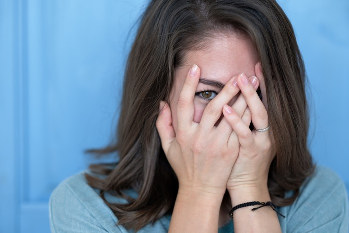 Studio shot of brunette girl hiding eyes under hand while feeling ashamed. Caucasian young woman in white shirt covering face with hand. Human facial expressions and emotions