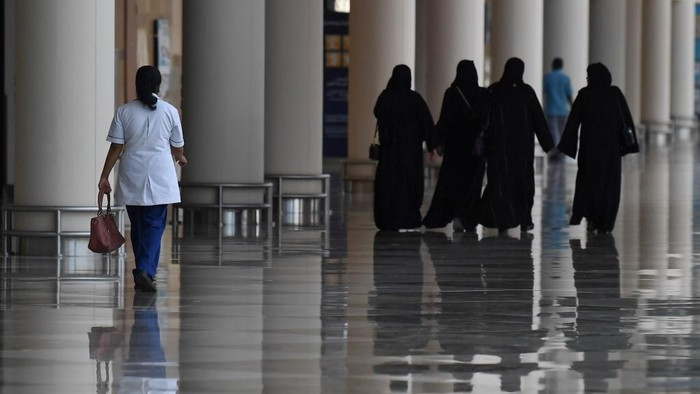 Emirati women walk in a nearly deserted shopping centre during the novel coronavirus pandemic crisis in the Gulf Emirate of Dubai, on April 19, 2020. (Photo by KARIM SAHIB / AFP)