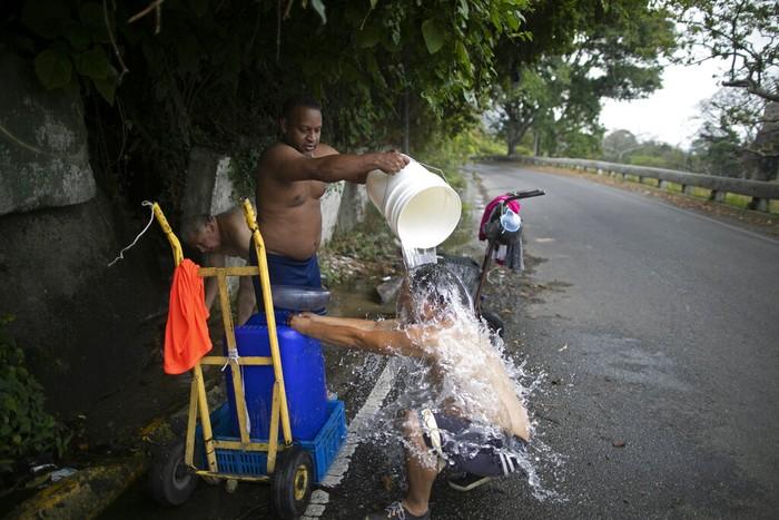 Warga tengah mandi di pinggir jalan di kawasan Caracas, Venezuela, kemarin. Ditengah perayaan Hari Bumi Internasional pada Rabu (22/4) dan ditengah berlangsungnya wabah virus Corona, banyak warga Caracas kesulitan air. AP / Ariana Cubillos
