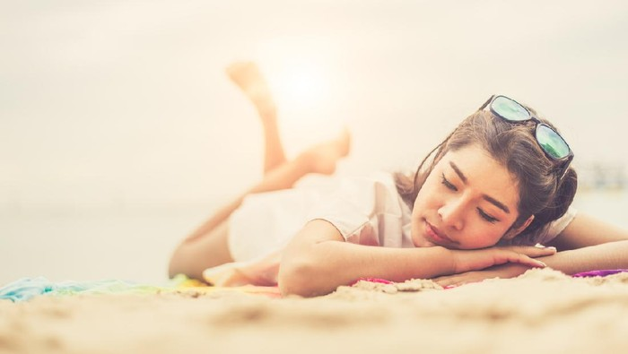 Beauty woman lying on beach. Sea and ocean background People and lifestyles concept. Vacation and relaxation theme. Summer seasonal theme.
