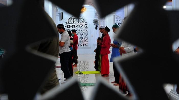 Umat Islam melaksanakan shalat Isya berjamaah di Masjid At-Taufiq, Jambi, Kamis (23/4/2020) malam. Sejumlah masjid di daerah itu terpantau tidak menggelar shalat Tarawih pada awal Ramadhan 1441 Hijriah. ANTARA FOTO/Wahdi Septiawan/aww.