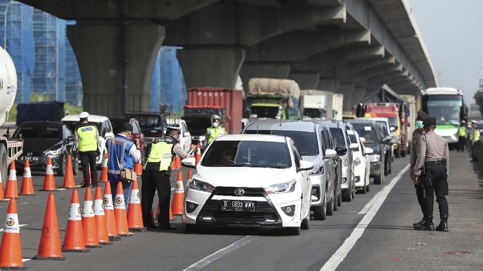 Indonesian police check a car passenger at a checkpoint during the imposition of large-scale restriction to curb the spread of the new coronavirus outbreak on a toll road in Cikarang, West Java, Indonesia, Friday, April 24, 2020. Indonesia is suspending passenger flights and rail service as it restricts people in the worlds most populous Muslim nation from traveling to their hometowns during the Islamic holy month of Ramadan because of the coronavirus outbreak. (AP Photo/Achmad Ibrahim)