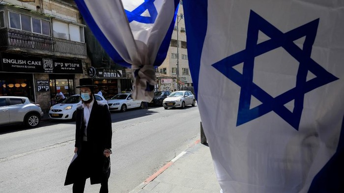 An Ultra-Orthodox Jewish man, wearing a surgical mask due to the COVID-19 coronavirus pandemic, walks past Israeli flags set up in front of a shop ahead of Israels independence day due later in the week, in the centre of Jerusalem, on April 23, 2020. - Israel will celebrate its 72nd Independence Day on April 28-29 under novel coronavirus regulations, with official events and public celebrations cancelled. Israelis are required to wear faces masks when venturing outside in accordance to a governmental directive in order to combat the spread of COVID-19. (Photo by Emmanuel DUNAND / AFP)