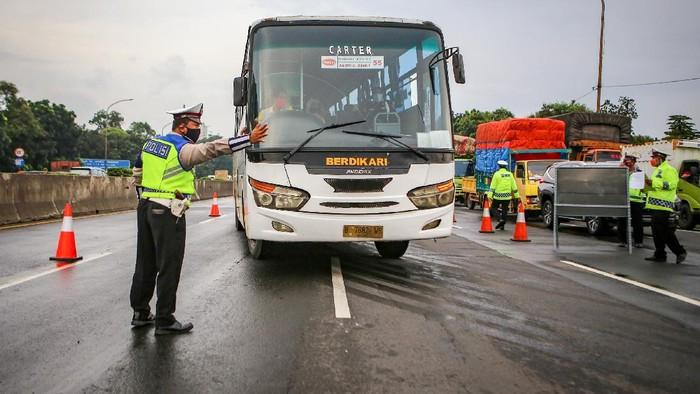 Petugas kepolisian berjaga saat dilakukan penyekatan kendaraan di pintu keluar Tol Bitung, Kabupaten Tangerang, Banten, Jumat (24/4/2020). Penyekatan itu dilakukan menyusul adanya larangan mudik bagi seluruh kalangan yang sudah ditetapkan mulai hari ini guna mencegah penyebaran COVID-19. ANTARA FOTO/Fauzan/wsj.
