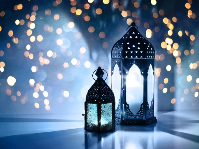 Couple of glowing Moroccan ornamental lanterns on the table. Greeting card, invitation for Muslim holy month Ramadan Kareem, festive blue night background with glittering golden bokeh lights.