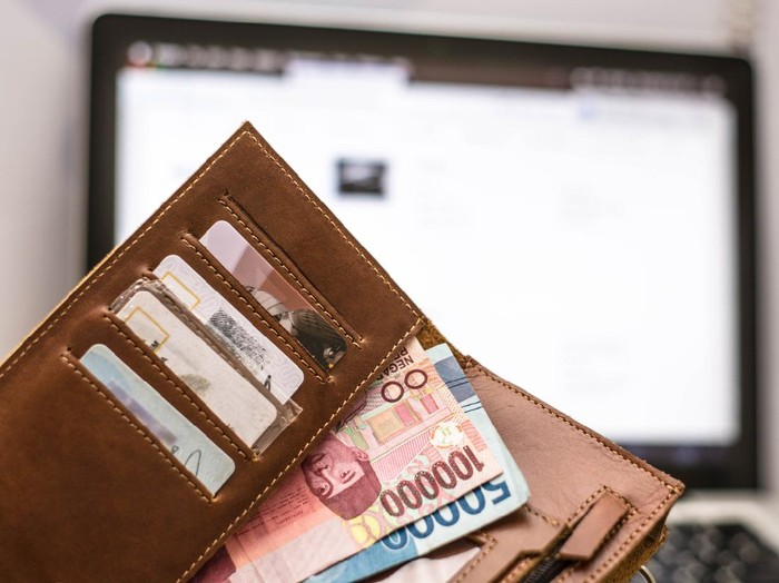wallet with rupiah money inside in front of computer laptop monitor screen, online transaction concept