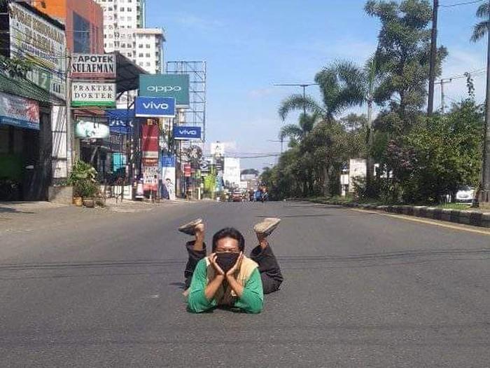 Warga berpose santai di tengah jalan yang sepi