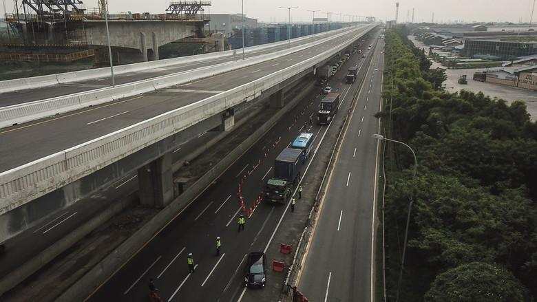 Petugas kepolisian membuat cek point pemeriksaan di dalam tol Jakarta Cikampek. Hal itu dilakukan untuk cegah warga mudik guna putus rantai penyebaran COVID-19.
