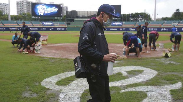 Petugas menyemprotkan disinfektan ke lapangan selama gelaran Liga Bisbol Taiwan. (