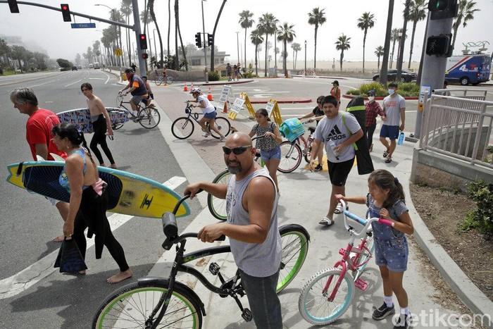 DI tengah pandemi Corona, warga Amerika Serikat justru memadati pantai akhir pekan lalu. Mereka tak mau melewatkan sensasi berjemur di pantai saat musim panas.