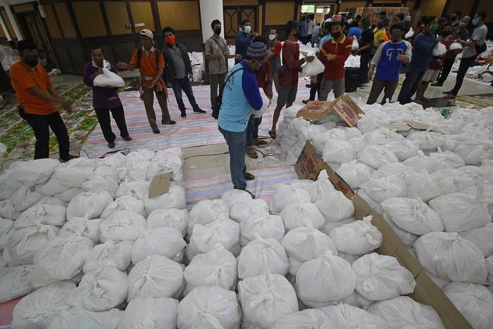 Relawan membungkus paket sembako bantuan dari berbagai perusahaan di Convention Hall, Surabaya, Jawa Timur, Minggu (26/4/2020). Bantuan sembako sebanyak 68.000 paket tersebut akan didistribusikan oleh Pemerintah Kota Surabaya kepada masyarakat berpenghasilan rendah (MBR) di 31 kecamatan yang terdampak COVID-19. ANTARA FOTO/Moch Asim/aww.