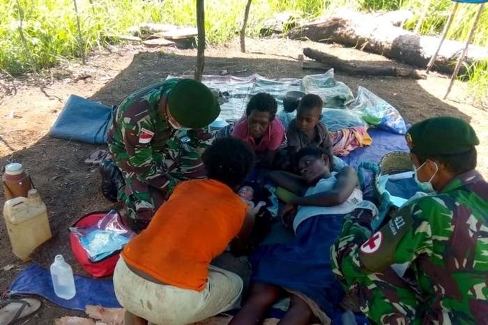 Personel kesehatan Satgas Pamtas RI-PNG Yonif MR 411/Pdw Kostrad membantu persalinan Ibu Apolina Maywa (24 th) warga RT 03 Yakyu, Kampung Rawa Biru, Distrik Sota.