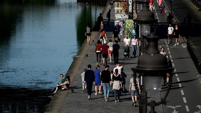 People walk along the Ourc canal during a sunny Sunday in Paris on April 26, 2020 despite a strict lockdown to stop the spread of the Covid-19 pandemic caused by the novel coronavirus. (Photo by Philippe LOPEZ / AFP)