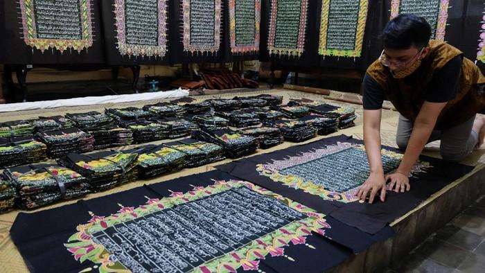 Perajin membuat batik motif ayat Alquran di Mahkota Batik Laweyan, Solo, Jawa Tengah, Senin (27/4/2020). Pemilik usaha batik setempat mengaku telah menyelesaikan mushaf Alquran sebanyak 30 juz lembaran batik bermotif ayat Alquran, yang selanjutnya untuk mengajak masyarakat belajar menulis, membaca dan memahami Alquran, sekaligus menarik kunjungan wisatawan di Kampung Batik Laweyan. ANTARA FOTO/Maulana Surya/hp.