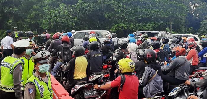 Petugas gabungan berjaga di Bunderan Waru di hari pertama penerapan PSBB Surabaya. Kendaraan pun menumpuk karena harus menjalani pemeriksaan.