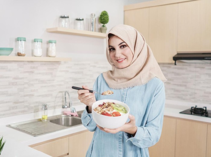 portrait of beautiful young woman wearing hijab with a bowl of granola with fresh fruit for breakfast