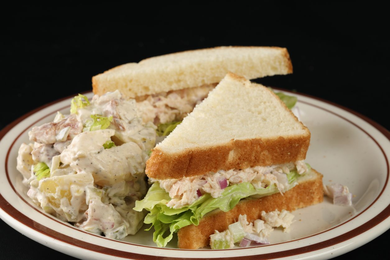 An extreme close up horizontal photograph of a tuna sandwich with potato salad on a white plate. Isolated on black.