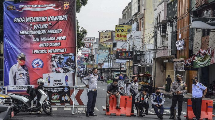 Sejumlah Polisi dan Petugas Dinas Perhubungan (Dishub) Kota Tasikmalaya berjaga di jalan yang ditutup sementara di Jalan Hz Mustofa, Kota Tasikmalaya, Jawa Barat, Selasa (28/4/2020). Penutupan jalan pusat Kota Tasikmalaya itu untuk memutus mata rantai penyebaran COVID-19 dan untuk menghidari terjadinya aktivitas masyarakat saat jelang berbuka puasa yang biasa disebut ngabuburit. ANTARA FOTO/Adeng Bustomi/hp.
