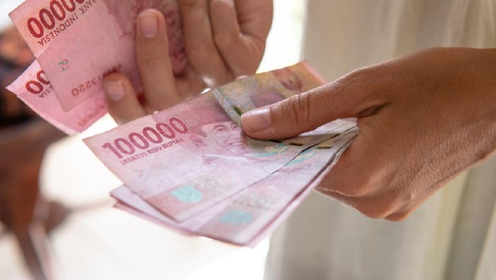 Girl recounts denominations of 100 thousand Indonesian rupees. Tourists Budget in Bali