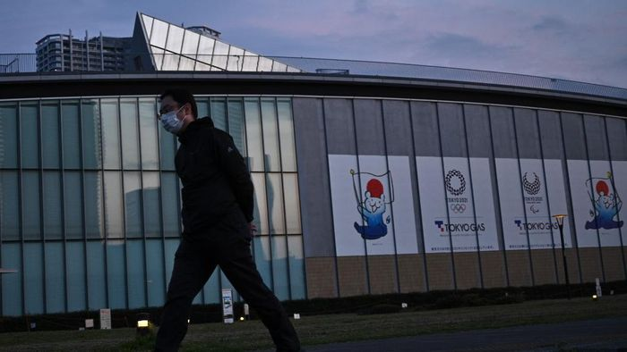 A man wearing a face mask walks past logos of the Tokyo 2020 Olympics along a promenade in Tokyo in April 7, 2020. - Japans Prime Minister Shinzo Abe on April 7 declared a month-long state of emergency in Tokyo and six other parts of the country over a spike in coronavirus cases. (Photo by Philip FONG / AFP)