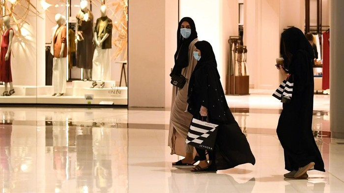 Women wearing masks for protection against the coronavirus, walk in the Mall of Dubai on April 28, 2020, after the shopping centre was reopened as part of moves in the Gulf emirate to ease lockdown restrictions imposed last month to prevent the spread of the COVID-19 illness. (Photo by Karim SAHIB / AFP)
