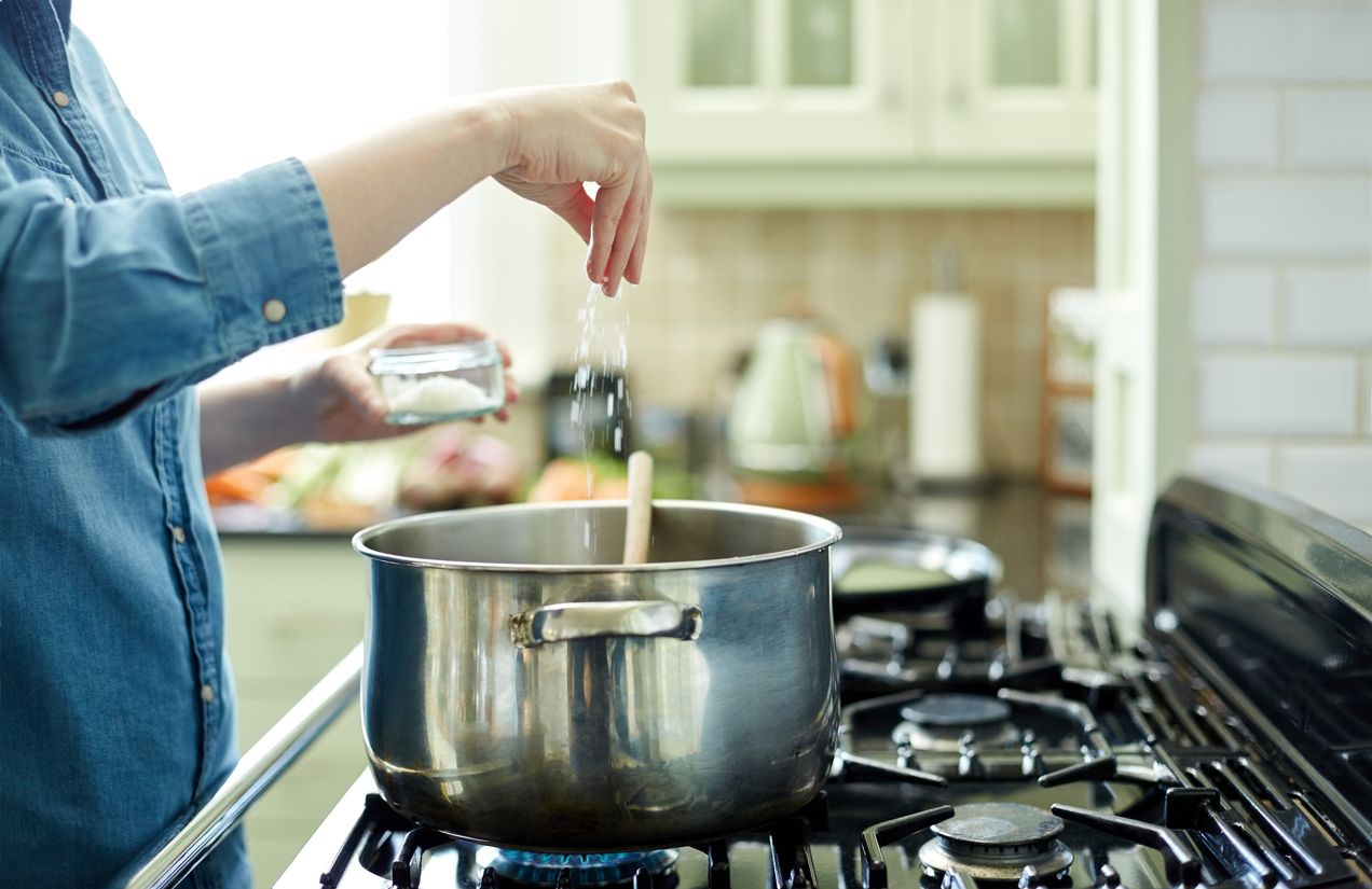 Midsection image of woman adding salt in cooking pot. Utensil is placed on gas stove. Close-up of female seasoning her dish. She is preparing food in domestic kitchen.