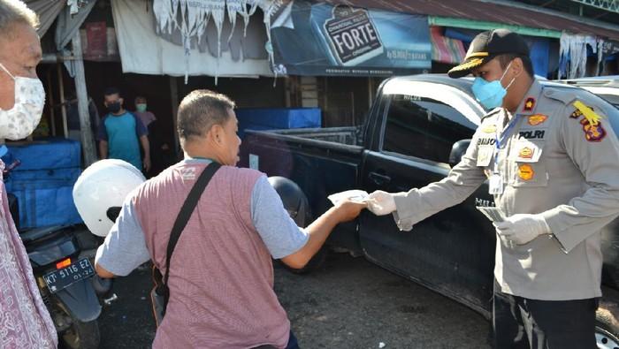 Polisi menjaga pasar tradisional di Paser, Kaltim, untuk memastikan warga dan pedagang memakai masker (dok. Istimewa)