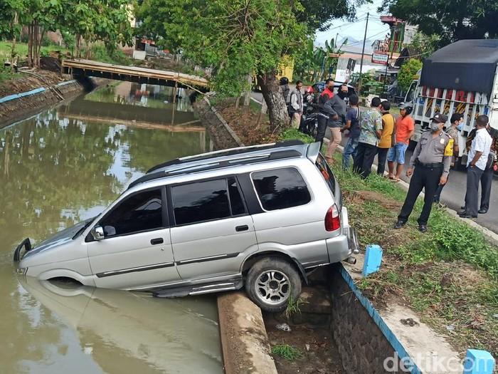 Mobil Isuzu Panther bernopol AE 1090 VE tercebur ke sungai di Jalan Ponorogo-Wonogiri KM 64. Pengemudi banting setir menghindari pemotor yang belok kanan.