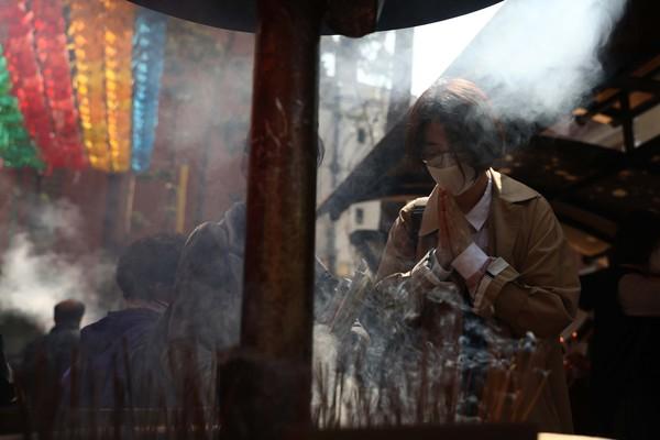 Umat Budha berdoa sambil dengan menyalakan dupa.