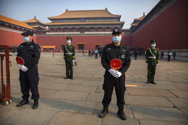 Sejumlah petugas keamanan berjaga dengan tetap memakai masker untuk mengantisipasi penyebaran virus Corona.