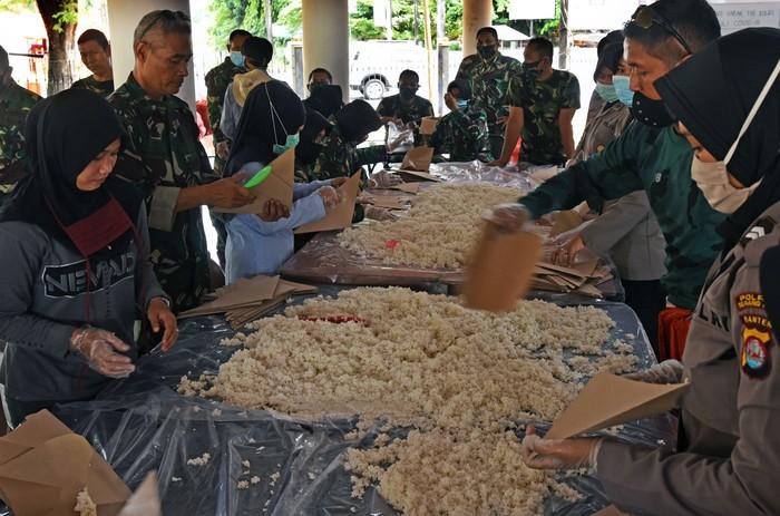 Sejumlah personel TNI dan Polri membungkus nasi saat membuka dapur umum di Alun-Alun Kota Serang, Banten, Jumat (1/5/2020). Dapur umum hasil kerja sama TNI-Polri tersebut setiap harinya akan membuat seribu bungkus nasi untuk warga terdampak pandemi COVID-19 dan akan dibuka untuk 20 hari ke depan hingga menjelang lebaran. ANTARA FOTO/Asep Fathulrahman/wsj.