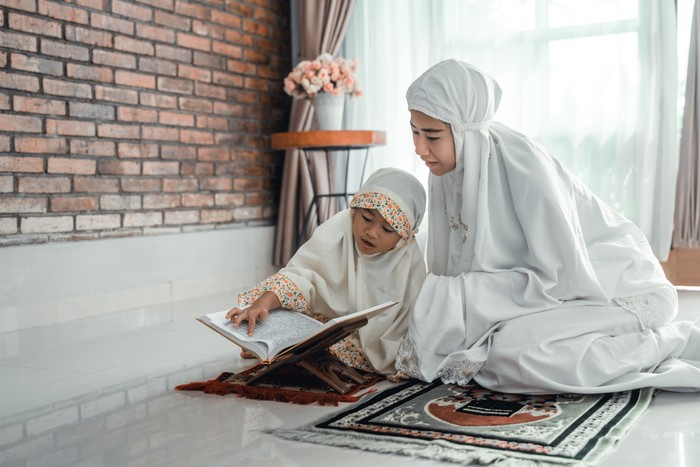 mother and kid reading quran together at home