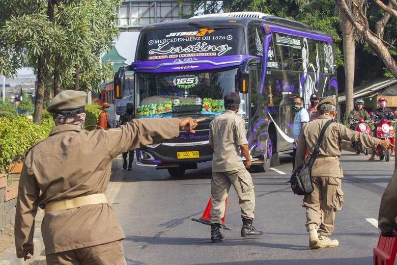 Petugas gabungan mengarahkan bus yang membawa pemudik dari arah Bekasi menuju Karawang untuk berputar arah di Perbatasan Karawang - Bekasi, Jawa Barat, Jumat (24/4/2020). Penyekatan akses transportasi di perbatasan tersebut sebagai tindak lanjut kebijakan larangan mudik yang berlaku bagi kendaraan pribadi, angkutan umum dan motor kecuali mobil pemadam kebakaran, angkutan logistik dan kebutuhan pokok serta ambulan. ANTARA FOTO/M Ibnu Chazar/pras.
