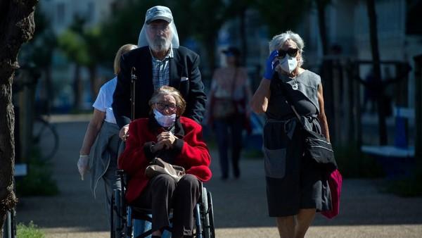 Kesempatan keluar rumah itu dimanfaatkan seluruh warga Spanyol, termasuk mereka yang menggunakan kursi roda.(AFP/ANDER GILLENEA)