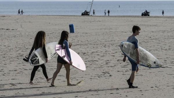 Warga di Pantai Valencia diberi waktu 48 jam untuk keluar rumah dan berolahraga sejak lockdown nasional diterapkan enam minggu lalu. (AFP/JOSE JORDAN)