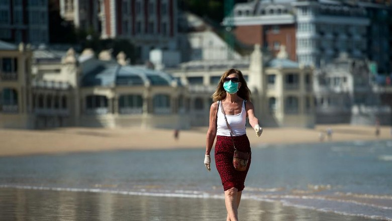 A woman wearing a face mask strolls on La Concha beach in San Sebastian, on May 2, 2020, during the hours allowed by the government to exercise, for the first time since the beginning of a national lockdown to prevent the spread of the COVID-19 disease. - All Spaniards are again allowed to leave their homes since today to walk or play sports after 48 days of very strict confinement to curb the coronavirus pandemic. After allowing children under 14 to go out since April 26, the government has again eased the conditions of the confinement imposed on March 14, which was one of the strictest in the world. (Photo by ANDER GILLENEA / AFP)