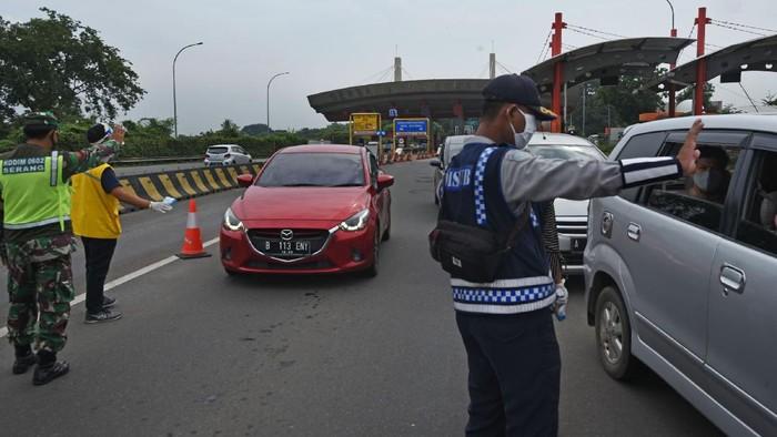 Petugas gabungan memeriksa kendaraan pribadi yang baru keluar dari pintu tol Serang Timur, di Serang, Banten, Rabu (29/4/2020). Penyekatan arus pemudik menuju Banten Selatan dan sekitarnya dilakukan guna menegakkan larangan pemerintah untuk mudik guna mencegah penyebaran COVID-19. ANTARA FOTO/Asep Fathulrahman/aww.