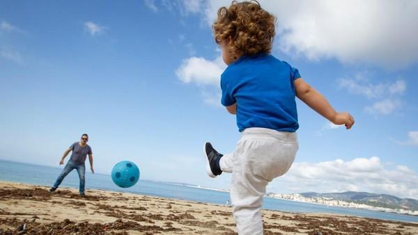 Kebijakan keluar rumah itu lebih dulu diterapkan kepada anak-anak. Seorang anak dan ayahnya bermain di Pantai Can Pere Antoni Beach di Palma de Mallorca, pada 26 April. (AFP/JAIME REINA)