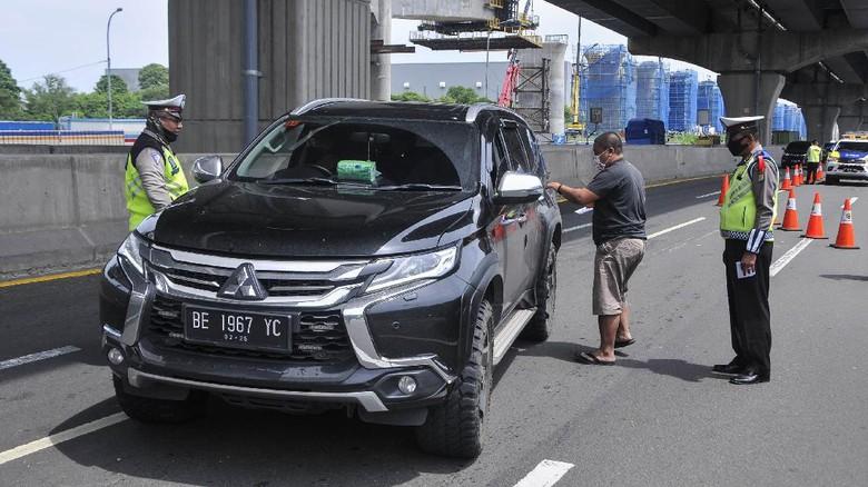 Sejumlah polisi menghentikan pengemudi kendaraan yang tidak menerapkan jarak sosial di tol Jakarta-Cikampek, Cikarang, Kabupaten Bekasi, Jawa Barat, Sabtu (25/4/2020). Penyekatan akses transportasi tersebut untuk membatasi pemudik dari Jakarta yang hendak ke luar kota menggunakan mobil pribadi, angkutan umum dan motor. ANTARA FOTO/ Fakhri Hermansyah/hp.