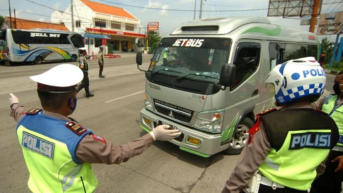 Petugas kepolisian memerintahkan mobil  travel untuk memutar kembali ke arah Jakarta saat penyekatan di jalur Pantura, Tegal, Jawa Tengah, Senin (27/4/2020). Penyekatan kendaraan pemudik oleh Polres Tegal Kota itu dilakukan menyusul adanya larangan mudik oleh Pemerintah guna mencegah penyebaran COVID-19. ANTARA FOTO/Oky Lukmansyah/hp.