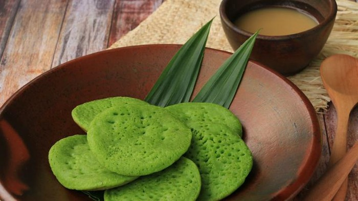 Javanese coconut milk and pandanus pancakes, served with sauce of coconut milk and palm sugar. Both the pancakes and the sauce are plated on traditional earthenware crockery set. Two wooden spoon are placed next to the plate. A folded woven straw mat lines the plate and cup. The meal is arranged on rustic wooden table that has a matching color with the earthenware. The image was taken outdoor using natural light.