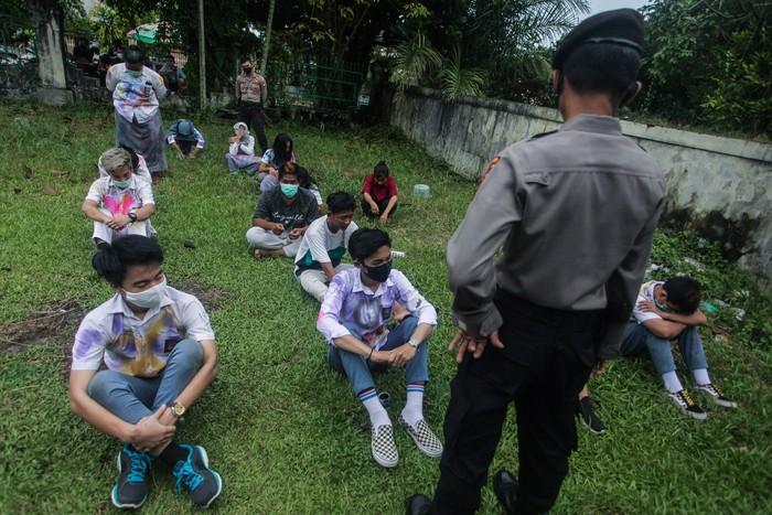 Polisi memberikan arahan ke sejumlah pelajar SMA yang terjaring razia saat melakukan perayaan kelulusan UN di kawasan kota Palangkaraya, Kalimantan Tengah, Minggu (3/5/2020). Personel Polda Kalteng membubarkan perayaan kelulusan tersebut dengan memberikan hukuman push-up dan mengimbau ke pelajar untuk tetap di rumah masing-masing guna mencegah penyebaran COVID-19. ANTARA FOTO/Makna Zaezar/aww.