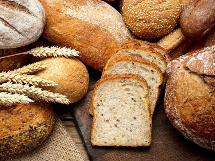 heap of various bread on wooden background