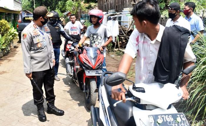 Polisi mengamankan puluhan pelajar SMK Kota Pasuruan yang akan melakukan konvoi kelulusan. Mereka kemudian dijemur dan disemprot disinfektan.