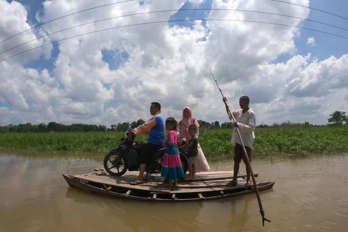Penyedia jasa perahu penyeberangan mengantarkan penumpang melintasi jalan penghubung Desa Jebus dengan Desa Gedong Karya yang terendam banjir di Muarojambi, Jambi, Senin (4/5/2020). Jalan penghubung desa satu-satunya di perbatasan Kabupaten Muarojambi dengan Kabupaten Tanjungjabung Timur itu terendam banjir luapan Sungai Batanghari dalam tiga pekan terakhir yang mengakibatkan akses jalan terputus untuk kendaraan atau hanya bisa dilewati perahu dan orang. ANTARA FOTO/Wahdi Septiawan/pras.