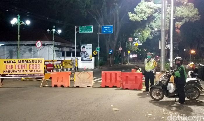 Memasuki hari kelima dan keenam penerapan PSBB di Sidoarjo, petugas memblokade total akses jalan di Waru pada malam hari. Suasana lengang bak lockdown sangat terasa.