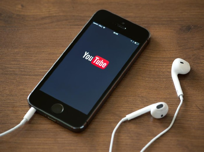Kiev, Ukraine - June 5, 2014: Brand new Apple iPhone 5S with YouTube application service on the screen lying on a desk with headphones. YouTube is the worlds most popular online video-sharing website that founded in February 14, 2005